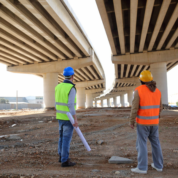 Two men looking up at the underside of a bridge - coating inspection